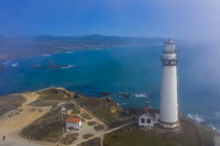 Aerial View Of A Lighthouse Off The California Coast As Fog Rolls In