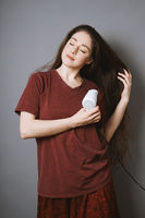 young woman blow-drying her long hair with blow dryer