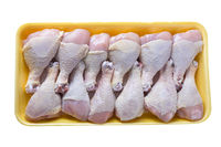 Raw chicken legs in  plastic tray on white background