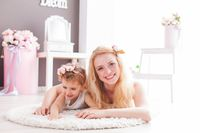 Lovely woman and girl on a soft carpet in their house