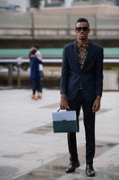 Full body shot of young African businessman with briefcase outdoors
