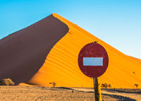 Stop sign in front of sand dune in Sossusvlei, Namib-Naukluft National Park, Namibia