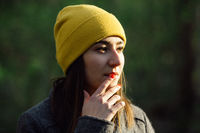 Young woman with red fingernails is wearing a yellow cap and touches her lips.