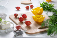 Ingredients for salad preparation, cheese, tomatoes, peppers, greens on a white kitchen table.