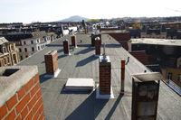 Blick auf ein Dach mit gemauerten Kaminen