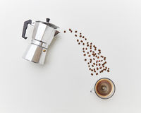Coffee beans pour in a cap with drink from a metal coffee maker on a white background. Flat lay