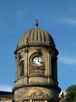 and ornate clock tower with stone cupola against a blue sky on the former sowerby bridge town hall