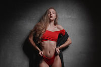 Woman in red bikini over gray wall studio background