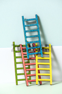 Multicoloured ladders on wall. Pastel tones. Concept for success and growth.