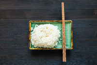 boiled rice and chopsticks on green plate on dark