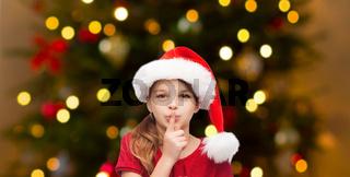 girl in santa hat over christmas tree lights