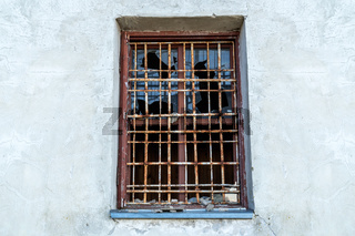 Broken glass window with bars