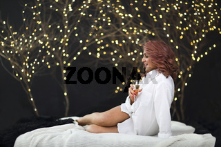 Smiling woman in white shit with glass of champagne over lights background
