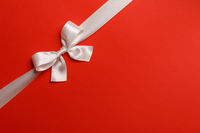 Shiny white ribbon bow on red