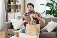 smiling man unpacking takeaway food at home