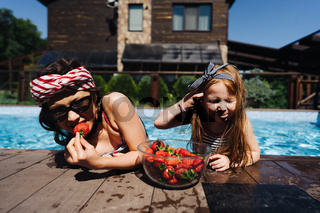 Two little girls on the side of the pool