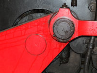 details of black steam locomotive wheel with red drive and connecting rods with bolts and leaking oil