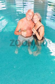 Senioren Paar mit einem Glas Sekt im Pool