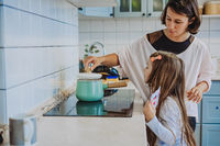 A little cute girl and her mother in the kitchen at home
