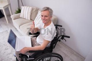 Disbaled man using laptop.