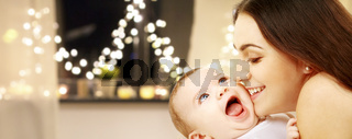 close up of mother with baby over christmas lights