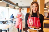Junge lächelnde Frau als Kellnerin serviert Vorspeisen