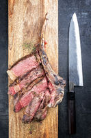 Barbecue dry aged wagyu tomahawk steak sliced as top view with a Japanese knife on a wooden board