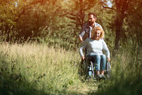 Happy woman in wheelchair with her husband. Outdoors