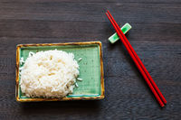 boiled rice on green plate and red chopsticks