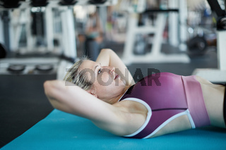 Junge Frau im Fitnesscenter macht Crunches