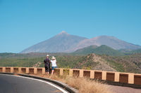 man and woman taking picture of summer landscape , mountain (Pico del Teide) and blue sky  background