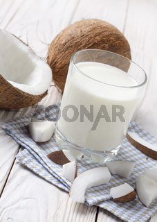 Drinking glass of milk or yogurt on blue napkin on white wooden table with coconut aside