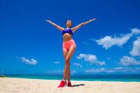 Happy fitness woman on beach