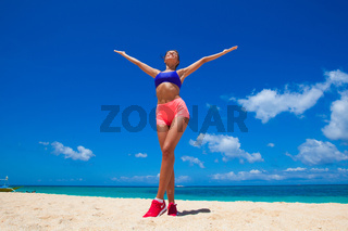 Happy fitness woman on beach