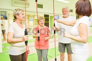 Senioren und Fitnesstrainer mit Schwingstab