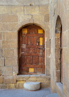 Old wooden door framed by arched bricks stone wall, Darb al Ahmar district, Old Cairo, Egypt