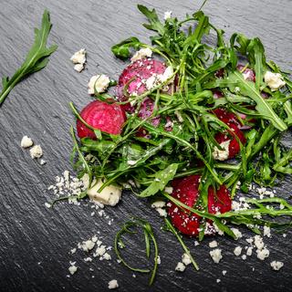 Beetroot arugula and feta cheese salad on slate stone plate closeup flat lay view