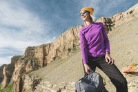 Smiling girl traveler in a yellow hat and a pair of sunglasses stands at the foot of epic rocks with a backpack next and looks away