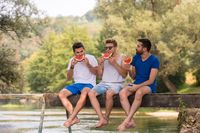 men enjoying watermelon while sitting on the wooden bridge