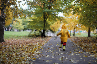 A child in a raincoat for a walk outside