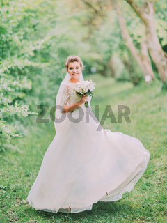 Full-length view of the smiling bride playing with the wedding dress in the green forest.