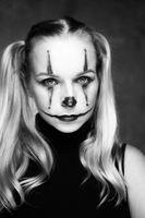 Halloween clown woman portrait posing over concrete wall background
