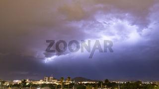 Purple Blue light illuminates the sky over the buildings homes and hills around Tucson Arizona