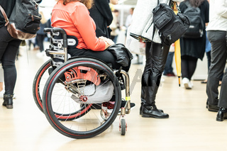 Close up of unrecognizable hanicapped woman on a wheelchair queuing in line to perform everyday tasks.