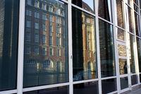 altes Gebäude am Alsterfleet spiegelt sich in Fenstern eines modernen Bürokomplex