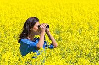 Woman looking through binoculars in blooming rapeseed field