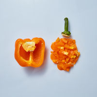 Fresh half pepper and finely chopped orange pepper on a gray background