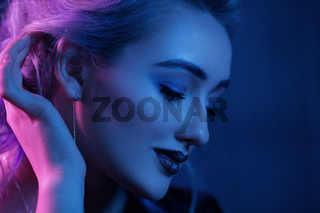 Beautiful woman with night makeup touching her hair. Close-up