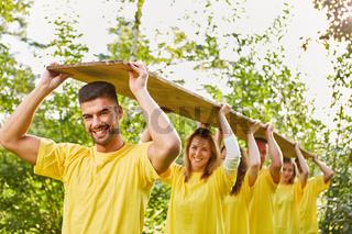 Junge Leute im Team tragen ein Holzbrett