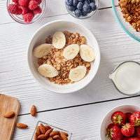 Healthy breakfast ingredients on a white woodwn background. Granola, nuts, berries, milk, banana in bowl , top view